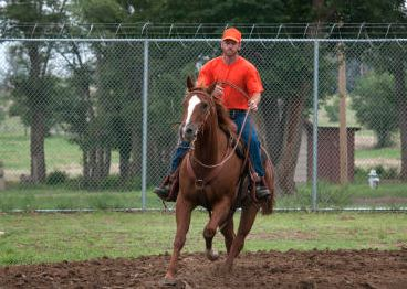ohn Taylor of Artesia, a former Marine, rides a horse named Romeo on the grounds of the Springer Correctional Center.